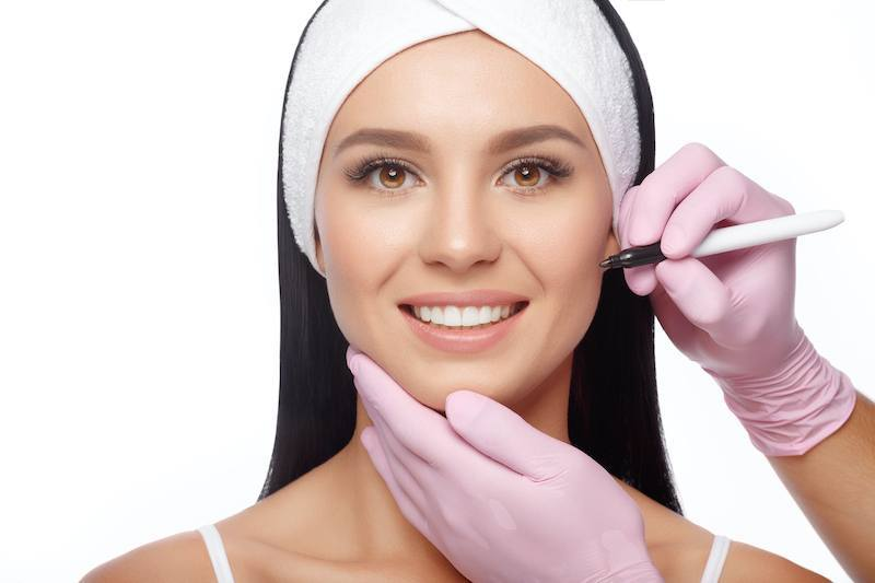 Young woman before plastic surgery operation. Beautician touch and draw correction lines on woman face. Woman face plastic operation. Beauty Face. Aesthetic face